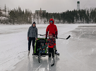 Two adults and children skate on a frozen lake