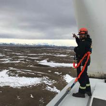 Otys Potts-Littlemustache, a wind turbine technician and member of the Piikani Nation, stands atop a wind turbine.