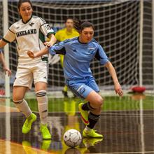 Women's futsal player Christine Moser battles for a ball in ACAC action.