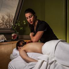 A massage therapy student practices with a fellow student.