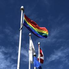 The Pride flag flying outside of the Lethbridge College campus.