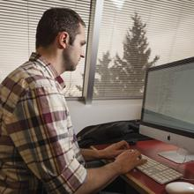 A Lethbridge College student at a computer.