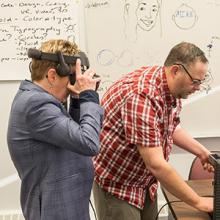 Instructor Mike McCready prepares Lethbridge College President and CEO Dr. Paula Burns to enter the world of virtual reality.