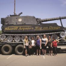 Students stand next to a tank